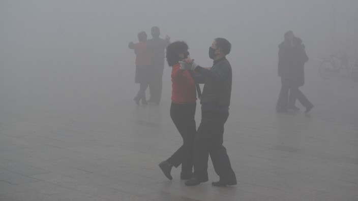 FILE PHOTO: People wearing masks dance amid heavy smog during a polluted day at a square in Fuyang