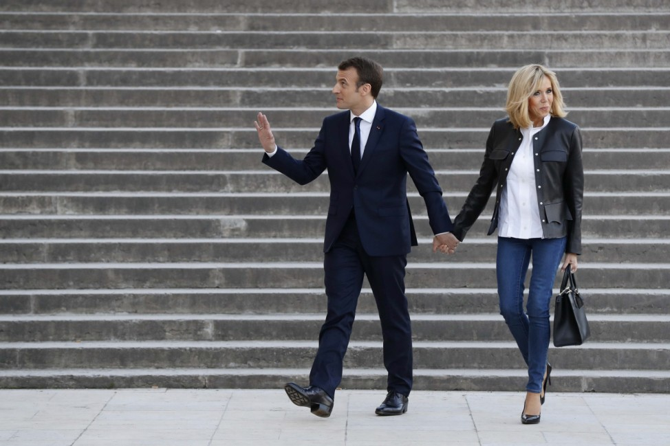 French President Emmanuel Macron, with his wife Brigitte Macron, arrives to attend an interview with journalists from BFM television and the Mediapart investigative website, at the Theatre National de Chaillot in Paris