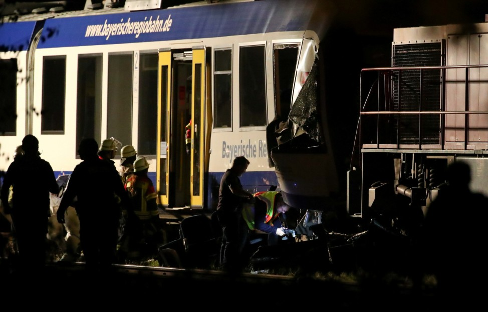 Firefighters and paramedics work at the scene where two trains collided in Aichach