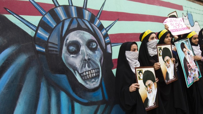 Iranian students holding pictures of Iran's Supreme Leader Ayatollah Ali Khamenei stand in front of an anti U.S. mural, painted on the wall of the former U.S. Embassy in Tehran
