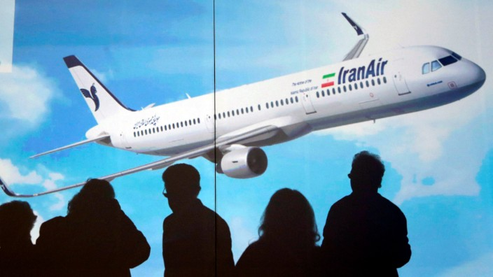 FILE PHOTO: Shadows of Airbus members are seen in silhouette in front of a poster of an A321 as IranAir takes delivery of the first new Western jet under an international sanctions deal in Colomiers