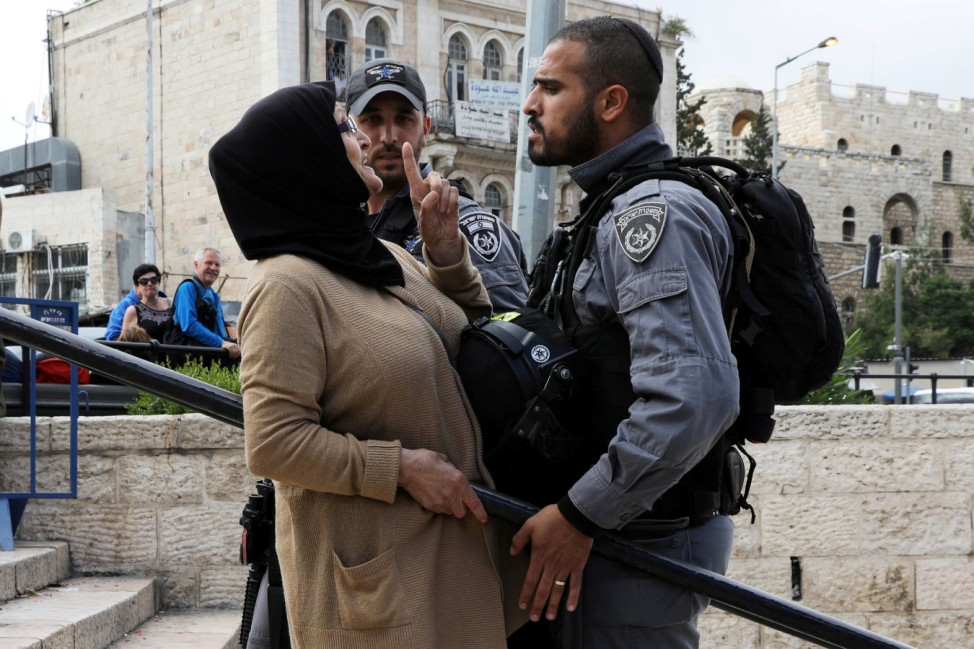 Israeli police officer argues with a Palestinian woman outside Jerusalem's Old City's Damascus Gate