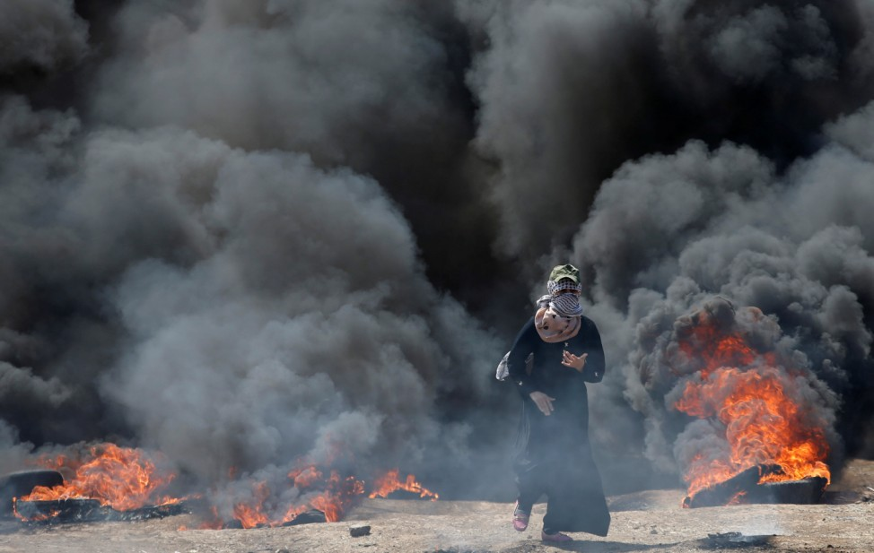 Female Palestinian demonstrator gestures during a protest against U.S. embassy move to Jerusalem and ahead of the 70th anniversary of Nakba, at the Israel-Gaza border, east of Gaza City