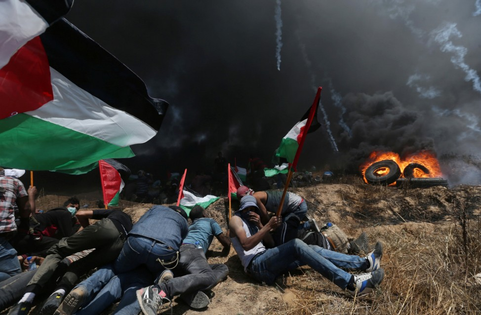 Palestinian demonstrators take cover from Israeli fire and tear gas during a protest against U.S. embassy move to Jerusalem and ahead of the 70th anniversary of Nakba, at the Israel-Gaza border in the southern Gaza Strip