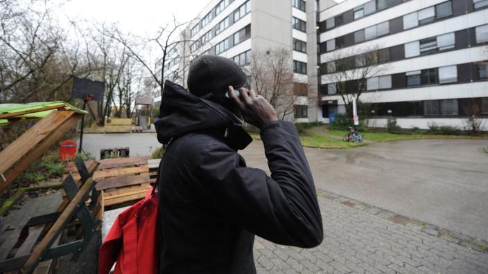 Ein Flüchtlinge telefoniert vor einer Gemeinschaftsunterkunft in München.
