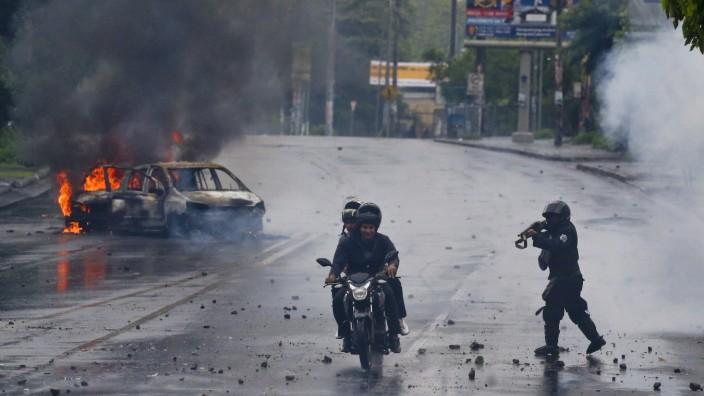 Proteste: Die Regierung sagt, sie sei für die Gewalt in Nicaragua nicht verantwortlich. Auf dem Bild ist ein Polizist zu sehen, der seine Schusswaffe auf einen Motorradfahrer und dessen Begleiter richtet, die an Protesten in der Hauptstadt Managua teilgenommen haben.