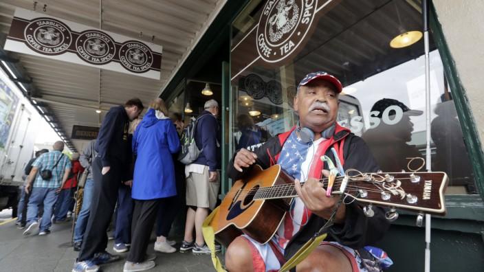 Seattle: Straßenszene in Seattle: Junge Angestellte holen sich einen Kaffe bei Starbucks, ein Mann spielt vor der Filiale für ein paar Dollar Gitarre.