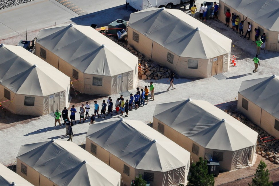 Immigrant children now housed in a tent encampment under the new 'zero tolerance' policy by the Trump administration are shown walking in single file at the facility near the Mexican border in Tornillo, Texas