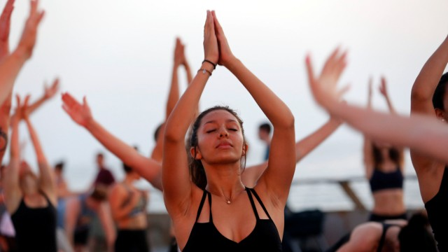 People practice Yoga on International Yoga Day in a port of Tel Aviv