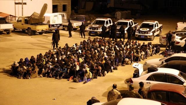 Polizei bewacht Flüchtlinge in Libyen.