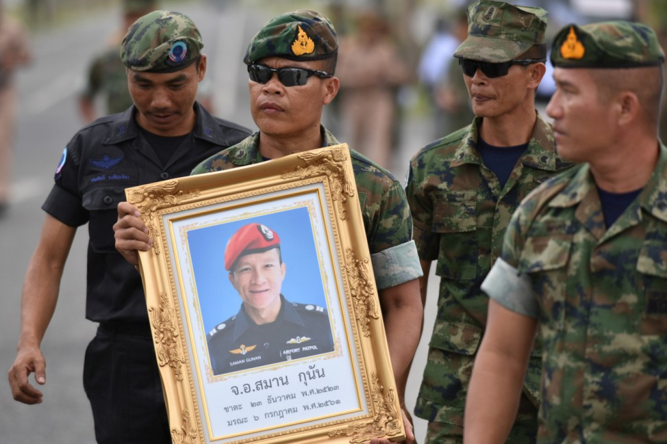 An honour guard hold up a picture of Samarn Poonan, 38, a former member of Thailand's elite navy SEAL unit who died working to save 12 boys and their soccer coach trapped inside a flooded cave as family members weep at a airport, in Rayong province