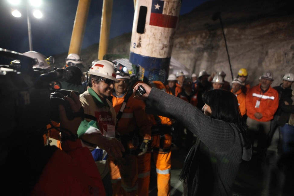 Miner Juan Carlos Aguilar is greeted by a relative after becoming the 29th miner to be rescued from the San Jose mine in Copiapo