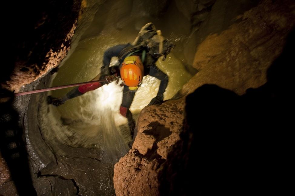 A caver descending through water in McBride's Cave.