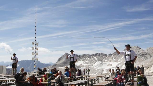 Goasslschnoizer take part in a whip cracking interlude on Germany's tallest mountain Zugspitze
