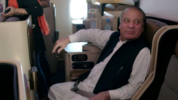 Ousted Pakistani Prime Minister Nawaz Sharif sits on a plane after landing at the Allama Iqbal International Airport