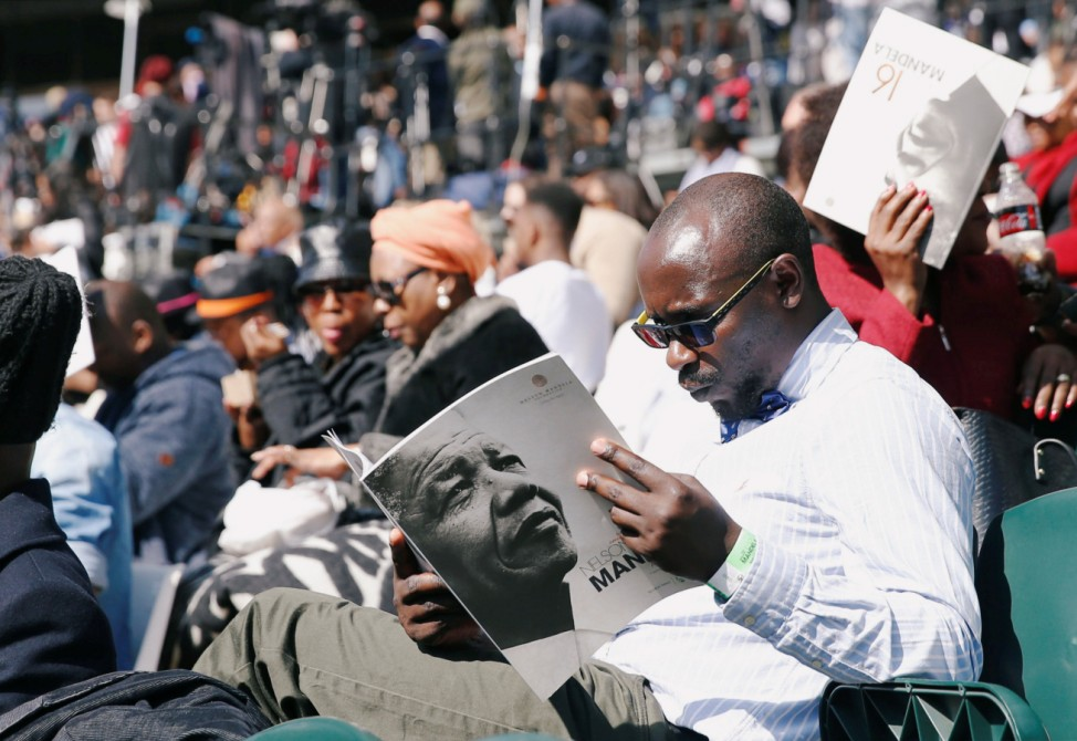A man holds a program as crowds gather to hear former U.S. President Barack Obama delivering the 16th Nelson Mandela annual lecture