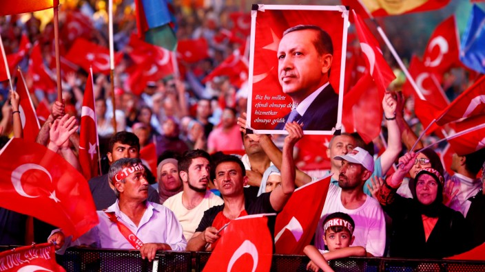FILE PHOTO: Supporters of Turkish President Erdogan wave national flags as they listen to him through a giant screen in Istanbul's Taksim Square