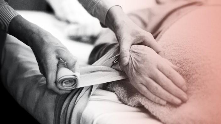 Eine Pflegerin fixiert die Hände einer verwirrten Altenheim Bewohnerin an das Bett um sie ruhig zu