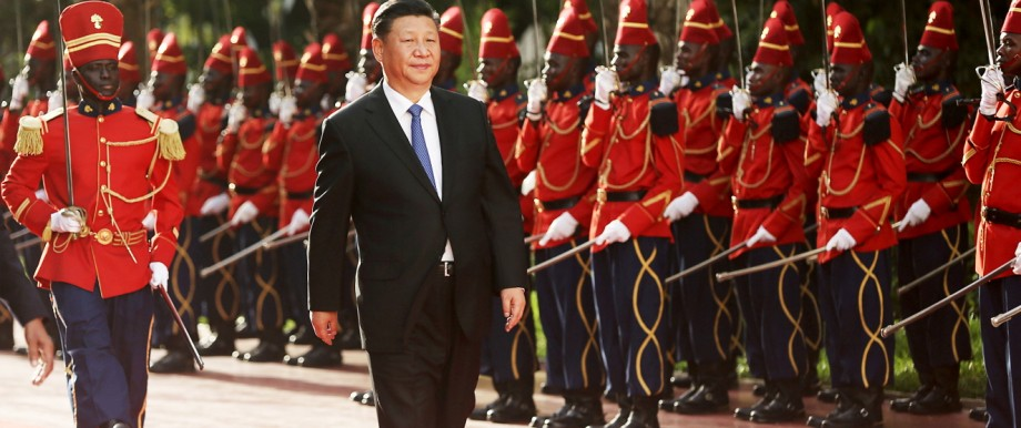 Chinese President Xi Jinping walks along the red carpet in front of a Guard of Honour at the Presidential Palace during his visit to Dakar
