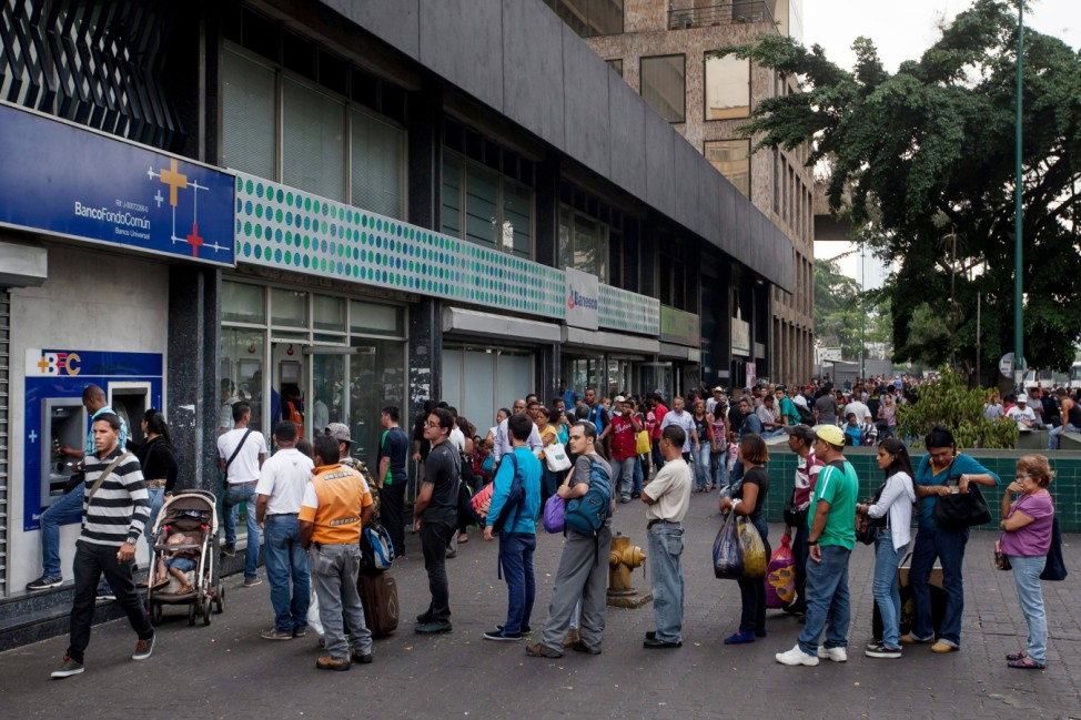 Venezuelans waiting to get cash from dispenser
