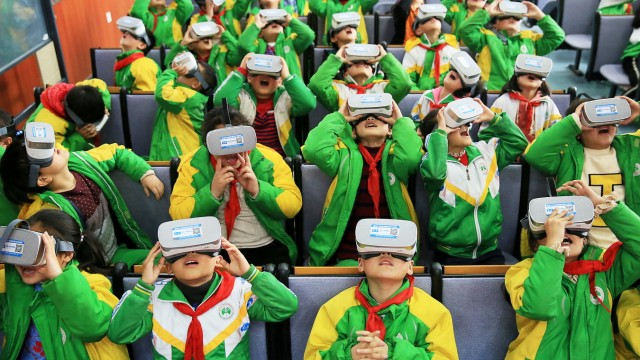 Primary school students wear virtual reality (VR) headsets inside a classroom in Xiangxi, Hunan