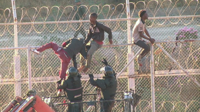African migrants in this still image from video climb the border from Morocco to Spain's North African enclave of Ceuta