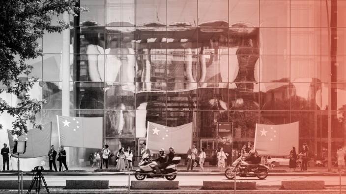 Stromnetz-Übernahme: Als vor Kurzem der chinesische Premierminister die Bundeshauptstadt besuchte, hießen ihn Zaungäste mit Flaggen vor dem Paul-Löbe-Haus Willkommen. In dessen Fassade spiegelt sich das Bundeskanzleramt.
