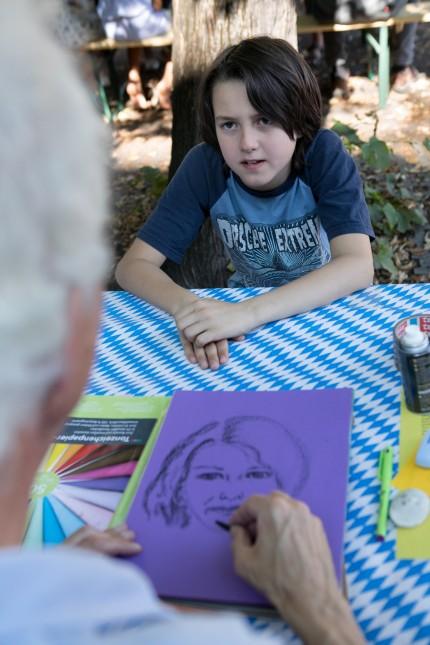 Kunstlehrer Andreas Wiehl zeichnet Portraits von Schülern am Sommerfest des Theresiengymnasiums (THG) am Kaiser-Ludwig-Platz 3