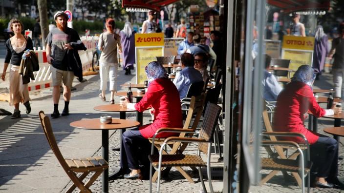 People walk down the sidewalk in Berlin's Kreuzberg district