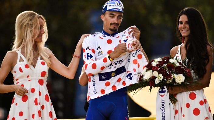 Sexismus im Sport: Zwei gepunktete Kleidchen und ein gepunktetes Trikot: Der beste Tour-de-France-Bergfahrer 2018, Julian Alaphilippe, erhält Ankleidehilfe.