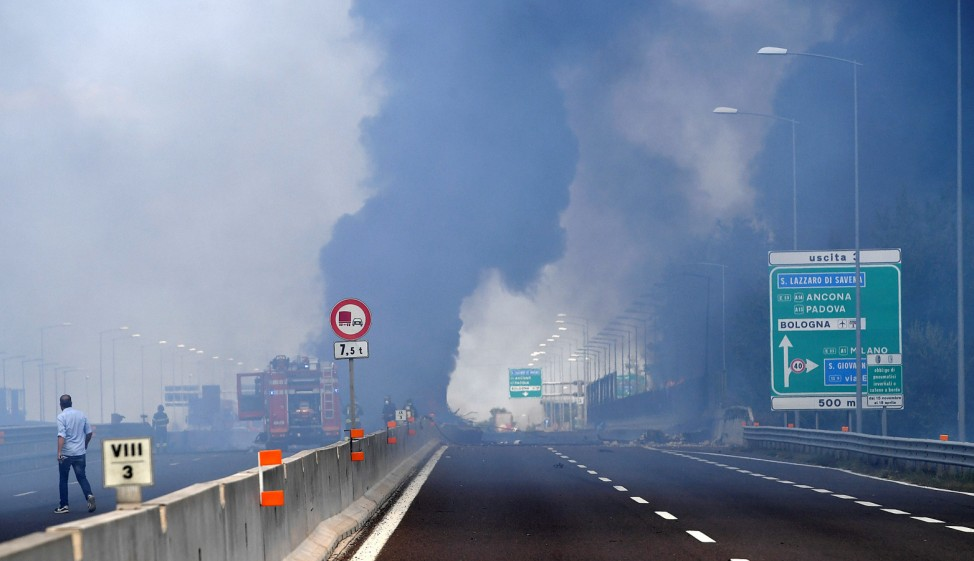 Firefighters work on the motorway after an accident caused a large explosion and fire at Borgo Panigale, on the outskirts of Bologna