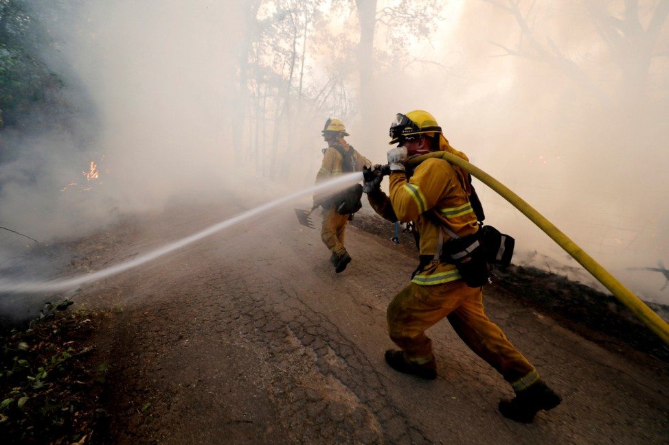 FILE PHOTO: Firefighter knocks down hotspots to slow the spread of the River Fire in Lakeport