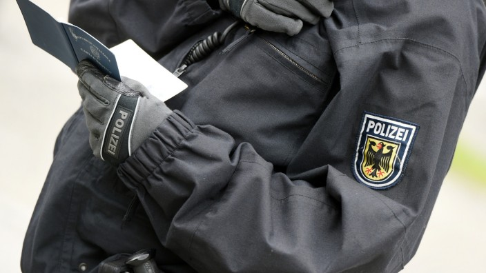 Ein Polizist überprüft Personalien bei einer Ausweiskontrolle