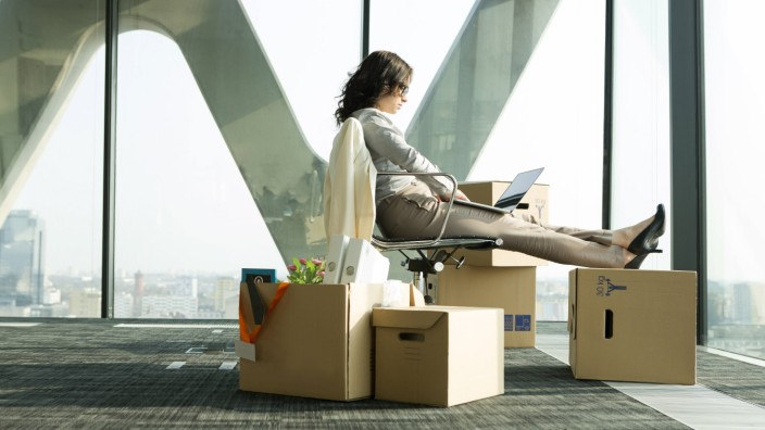Businesswoman using laptop with feet on cardboard boxes model released property released PUBLICATION