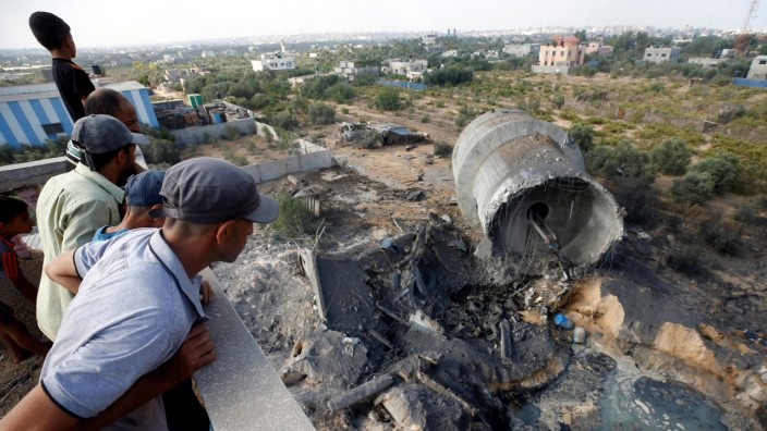 Palestinians look at damage at the site of an Israeli air strike in Al-Mughraqa on the outskirts of Gaza City