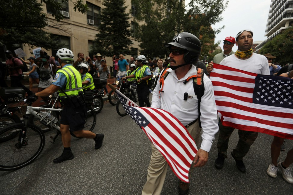 Supporters of white nationalist leader Jason Kessler march with a police escort in Washington