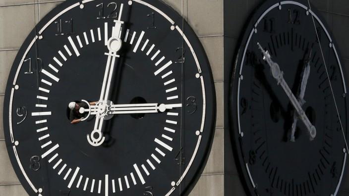 Worker adjusts hands on clock face of city administration building during clock's restoration in Krasnoyarsk