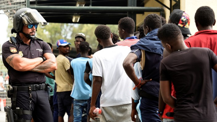 African immigrants wait in a row as they enter the immigrant center CETI in the Spanish enclave Ceuta, after some 200 refugees crossed the border fence between Morocco and Ceuta in the morning hours