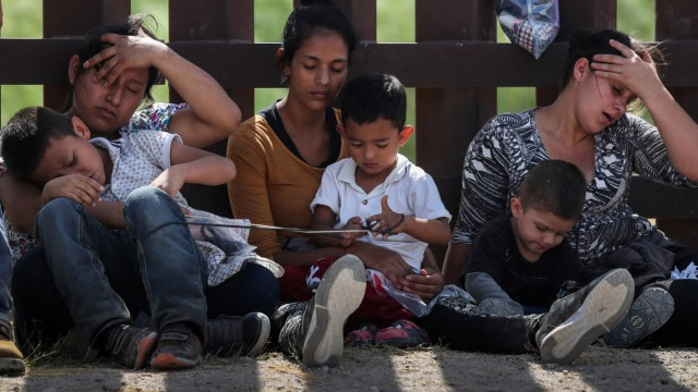 Immigrant women hold their children along the border wall as they await apprehension after illegally crossing into the U.S. from Mexico