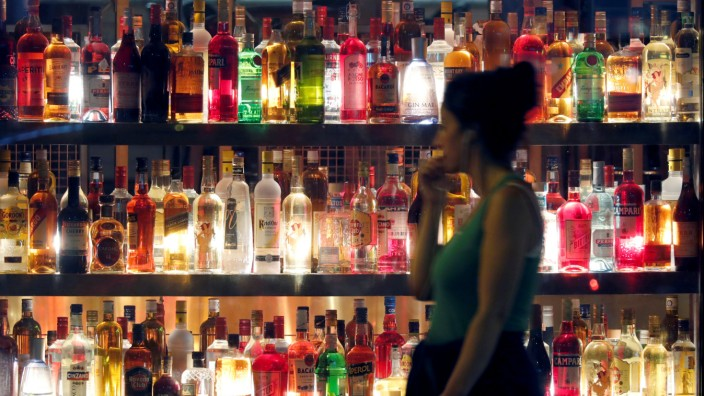 A woman walks past a restaurant's wall decorated with hundred of bottles in Paris