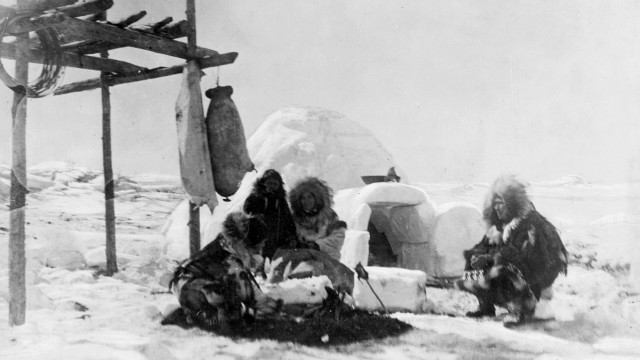 Grönländische Eskimos vor einem Iglu