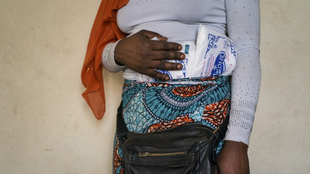 A Rwandan smuggler hides packets of plastic bags in her clothing as she prepares to smuggle them into Rwanda.