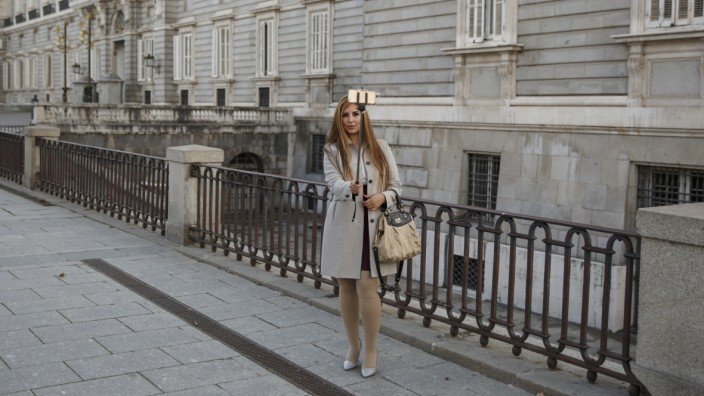 A woman takes a selfie outside Madrid's Royal Palace