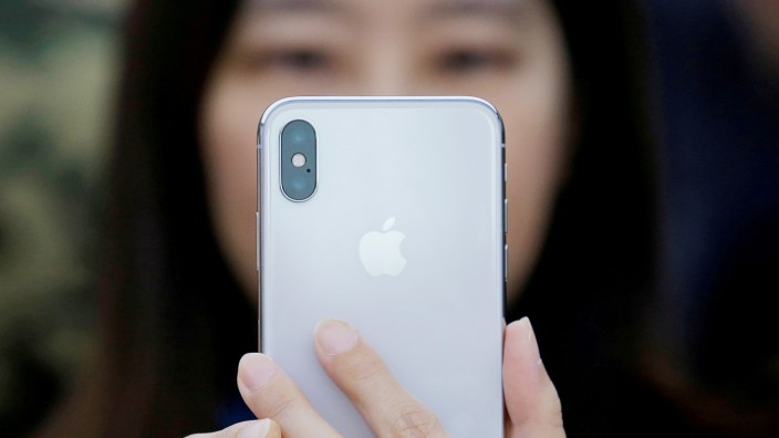 A attendee uses a new iPhone X during a presentation for the media in Beijing