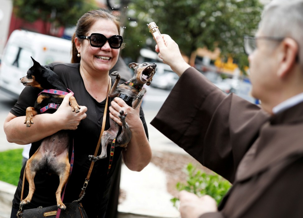 Woman holds her dogs as a priest blesses them outside Sao Francisco de Assis Church in Sao Paulo