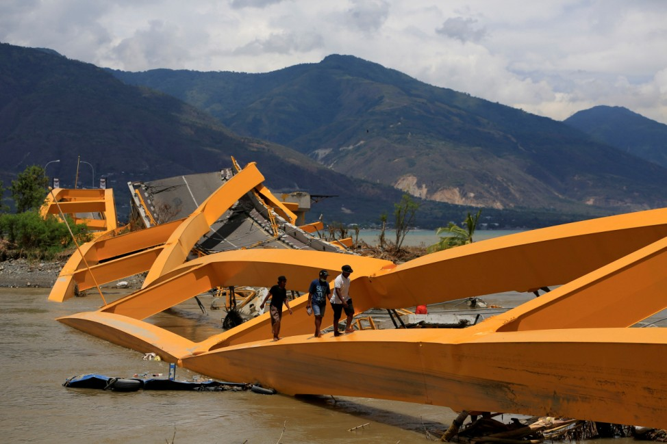 People walk on a broken bridge after it was hit by an earthquake and tsunami last week in Palu, Sulawesi island, Indonesia