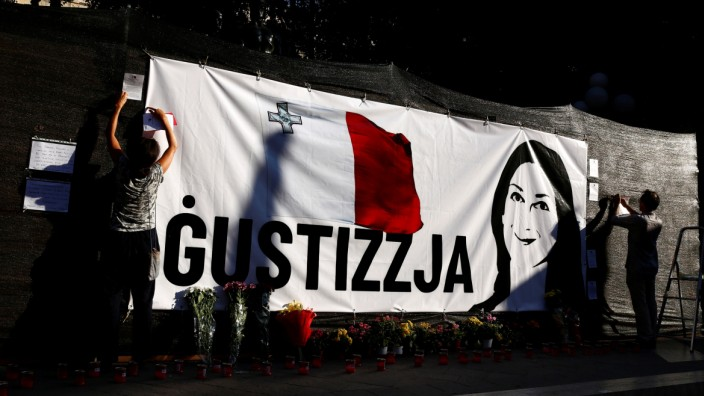 Activists, for the second time in a day, hang a banner demanding justice for assassinated anti-corruption journalist Daphne Caruana Galizia on hoarding surrounding the Great Siege monument, in Valletta