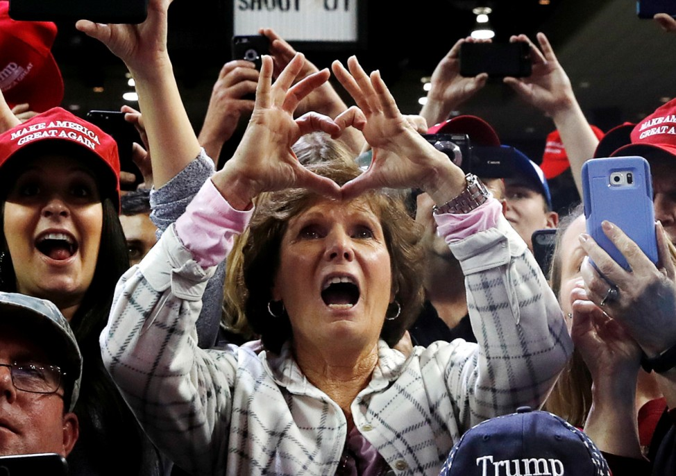 A woman forms the shape of a heart with her fingers during a campaign rally by U.S. President Donald Trump in Council Bluffs