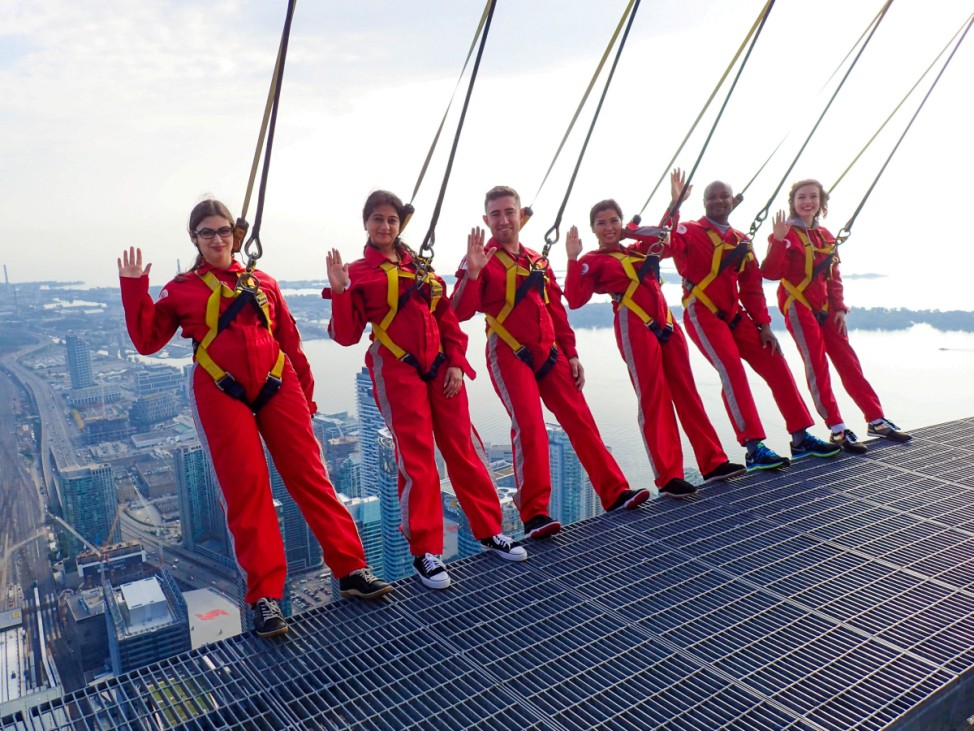 Six new Canadians pose while harnessed to the top of the CN Tower, before taking their oath of citizenship on the 'Edgewalk' above Toronto