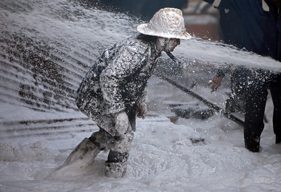 A firefighter is covered with AFFF as he tries to control a fire that broke out in a thinner manufacturing plant on the outskirts of Ahmedabad